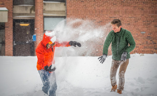 male snowing snowball at another student