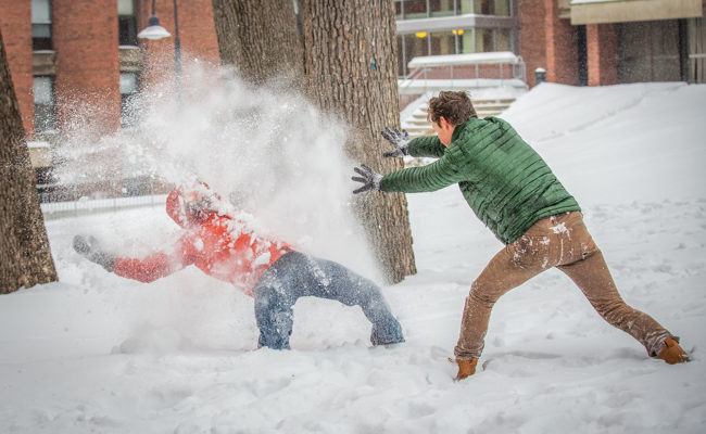 male student throwing snow at another student