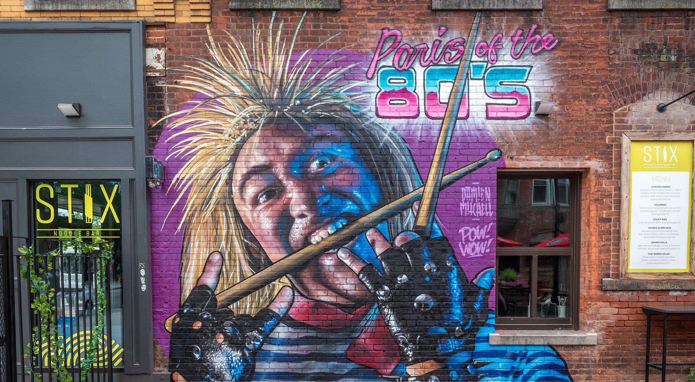 Mural of punk rocker on brick wall