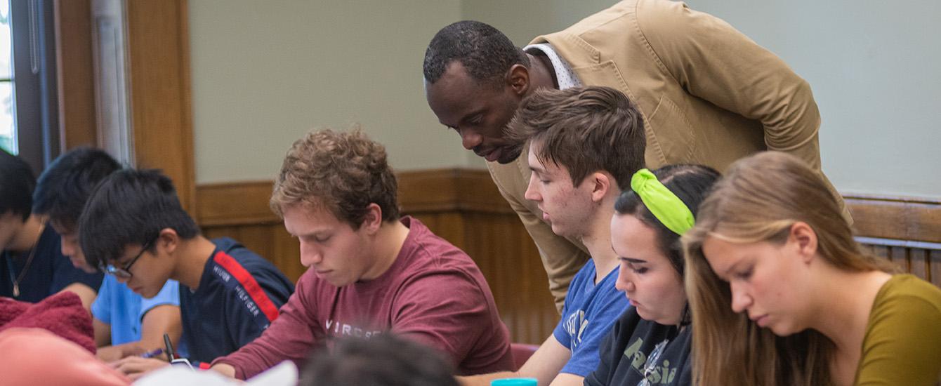 Professor looking over shoulder of student working in class