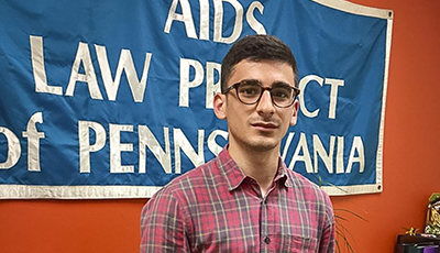 Student standing in front of AIDS sign