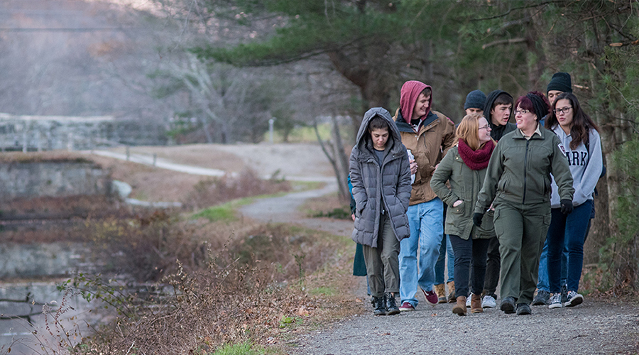 students walking down path near pond