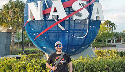 alum in front of nasa sign