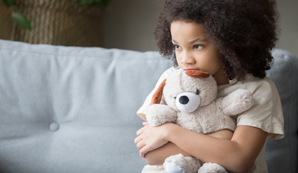 sad child hugging a teddy bear