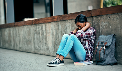 sad student sitting alone on sidewalk