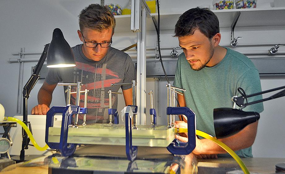 Physics students Nikolay Ionkin and Nathan Fitzpatrick look over a physics experiment