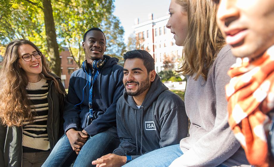 student workers sitting on stone wall