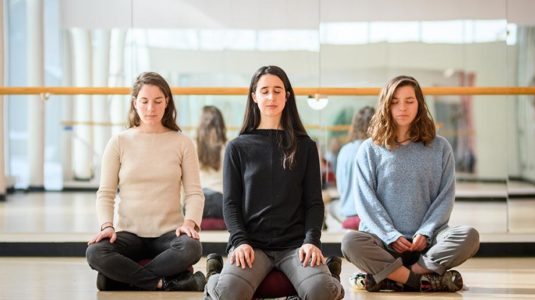 three students in yoga positions