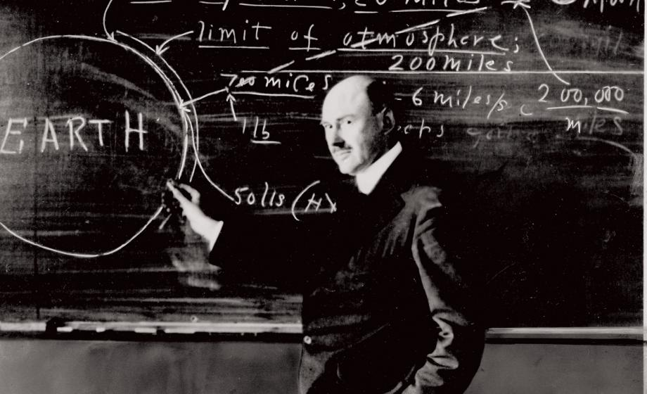 Robert Goddard posing with writings on a blackboard