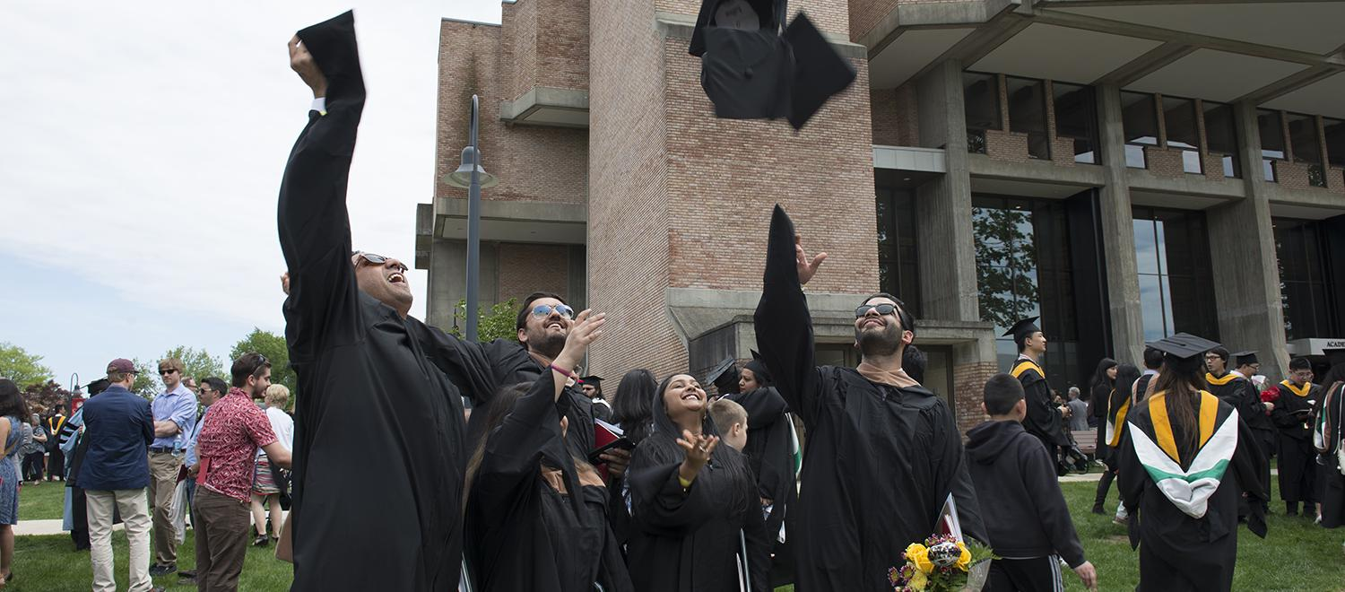 graduate students throwing hats in the a