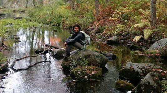 Olivia Barksdale sitting by stream