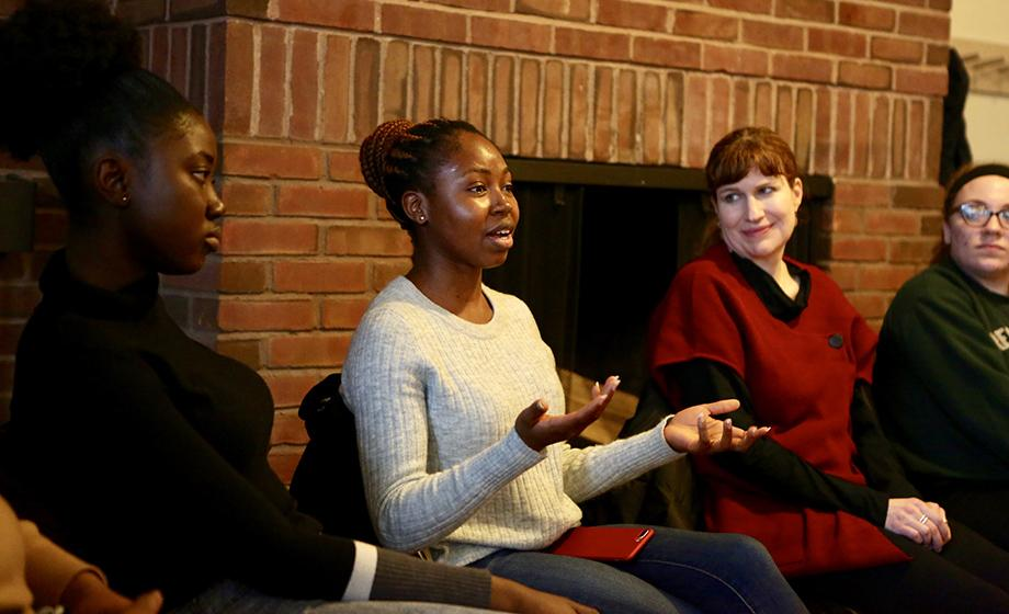female students sitting in front of fireplace discussing issues