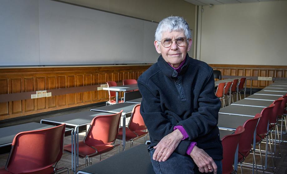 Professor Cynthia Enloe sitting on pupils desk