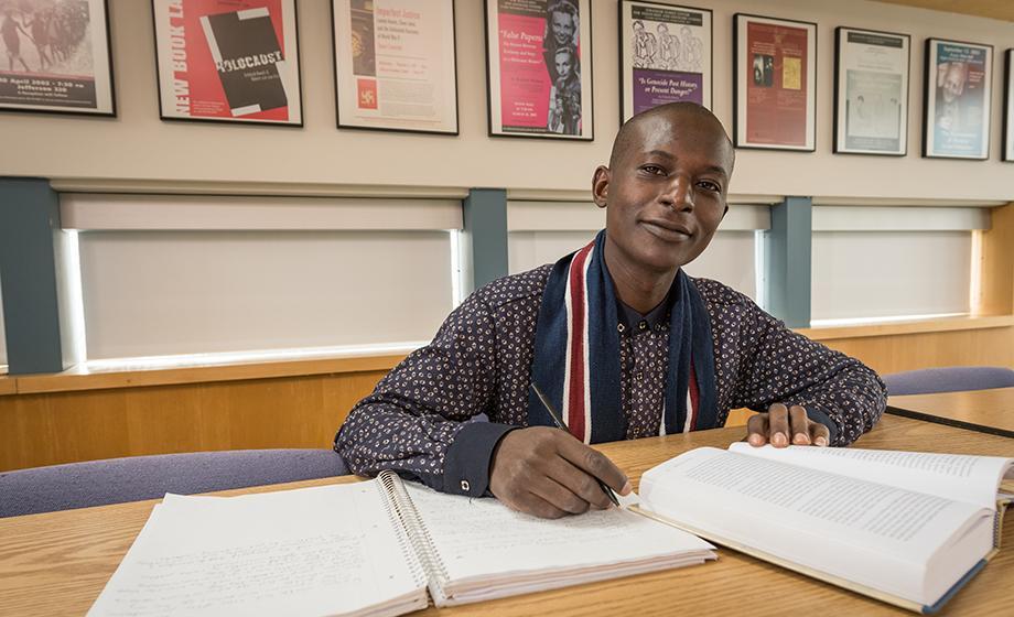 Victor Uhuru sitting at desk in library