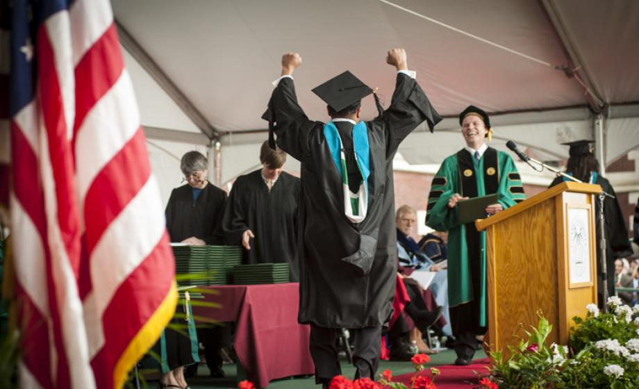 graduate student receiving diploma from President Angel