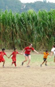 Clark University senior Rachel Spera, runs with youngsters during a sports camp led by Clark athletes visiting Guatemala in January.
