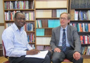 Clark University Ph.D. student Gbeton Somasse, left, meets recently with his adviser, Professor of economics Wayne Gray.
