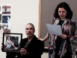 Belén Atienza, associate professor of Spanish, introduces poet and AIDS activist Norberto Stuart (seated) to students and guests in her classroom in Estabrook Hall, March 30.