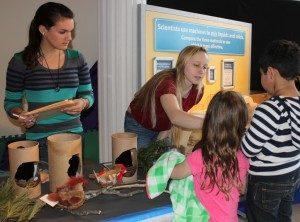 Sarah MacLachlan '14 and Savannah Sanford '17 watch as museum patrons guess city bird habitats