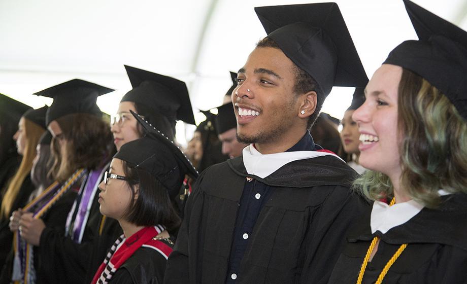 graduatre stueents standing up in tent