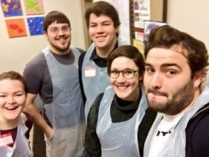 Pictured from left to right: Ali Gillard '18, Ben Gardner '12 and Sam Kennedy '18, pose with site leaders from Break a Difference at a food bank in NYC.