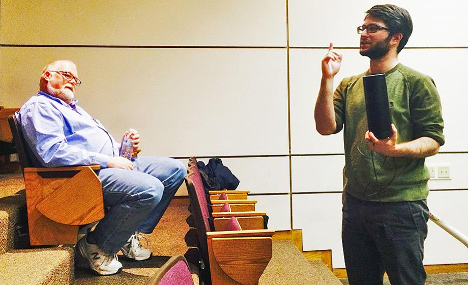 Jake Kramer talks to computer science students while holding an Amazon Echo speaker; visiting professor and former Amazon manager Kenneth Basye watches from the audience