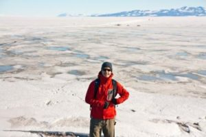 Luke Trusel, postdoctoral scholar at Woods Hole Oceanographic Institution, stands near sea ice covered in melt ponds at McMurdo Station in Antarctica, in 2010. Trusel received a Ph.D. in geography at Clark University in 2014.