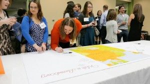 Leir Program alumni sign a map of The Grand Duchy of Luxembourg during the reunion.