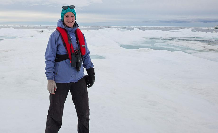 Meghan Kelly, a graduate student at Clark University, standing on land in the Arctic.