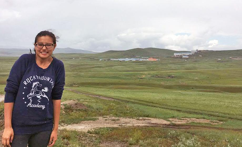 Odgerel Chintulga outside in Mongolia, with mountains in background