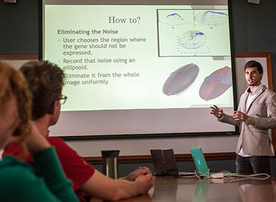 Teodor Nicola-Antoniu '19, an undergraduate student in Professor Jacqueline Dresch's lab, explains his research to fellow students during Dresch and Robert Drewell's combined biology- mathematics lab meeting.