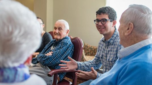 Jeremy Maltz '20, right, listens to retirees describe their technology experience; at left is alumnus Kenneth Hedenburg '50, who has a degree in business administration from Clark.