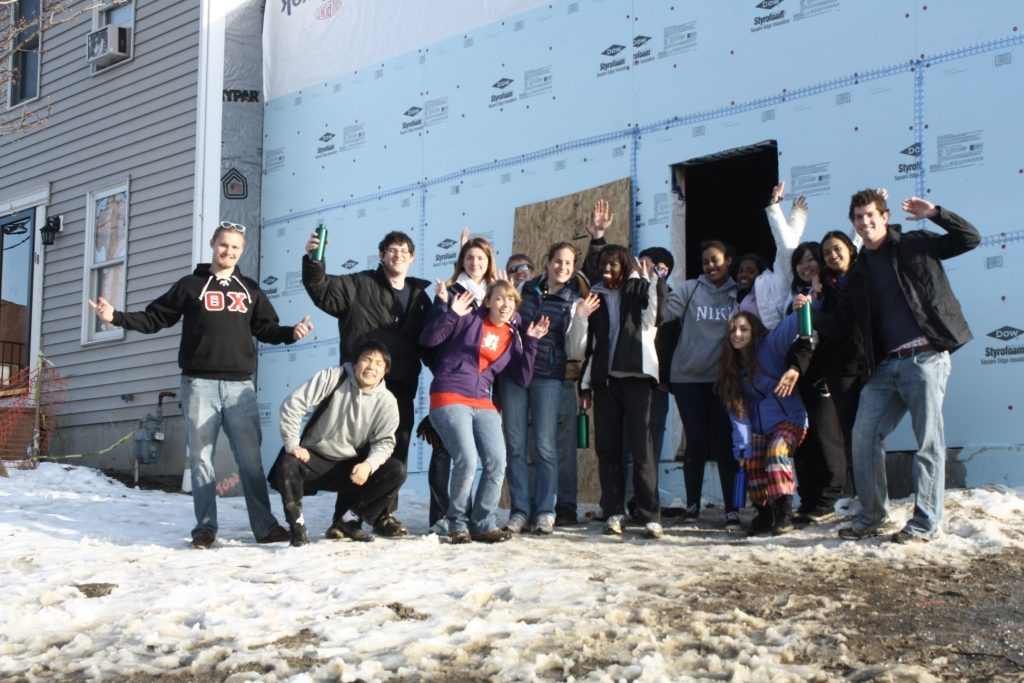 Team members celebrate the completion of their task, building a house in the Clark neighborhood.