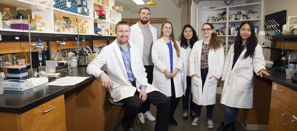 From left, Donald Spratt and five of the 14 students currently working his lab: seniors Noah Schwaegerle, Roela Bardhi, Emlie Ogisu, Lara Prosterman and Pinky Htun.