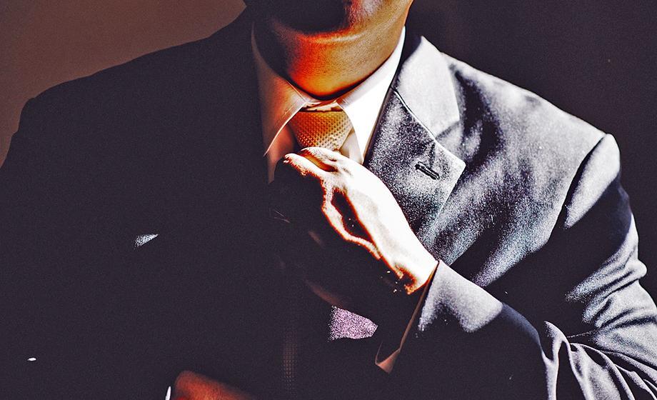 photo of man fixing his tie