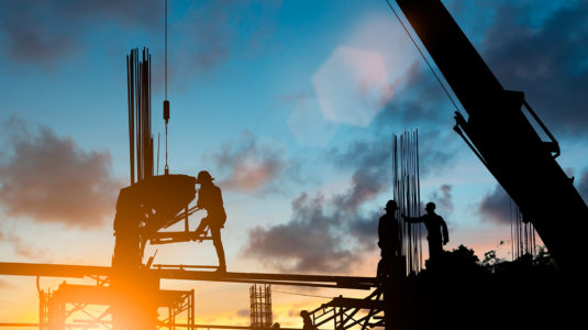 Silhouette of construction workers at site, with sun setting