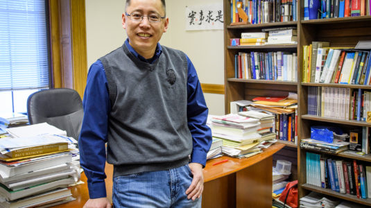 Junfu Zhang standing in his office