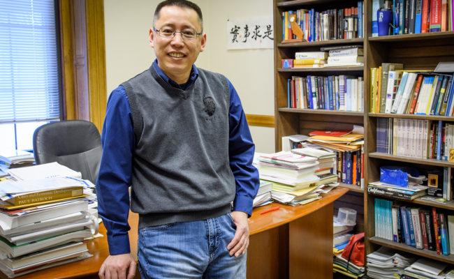 Junfu Zhang standing in his office