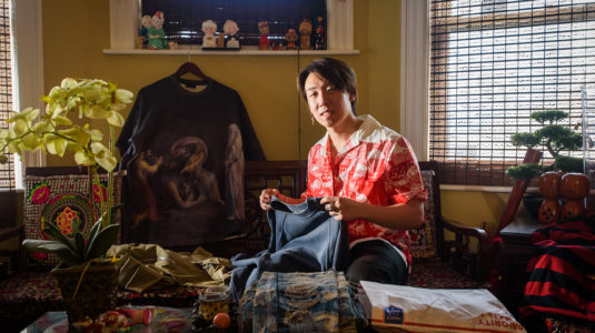 Kendrick Quek sits in his living room and holds up his vintage fashion