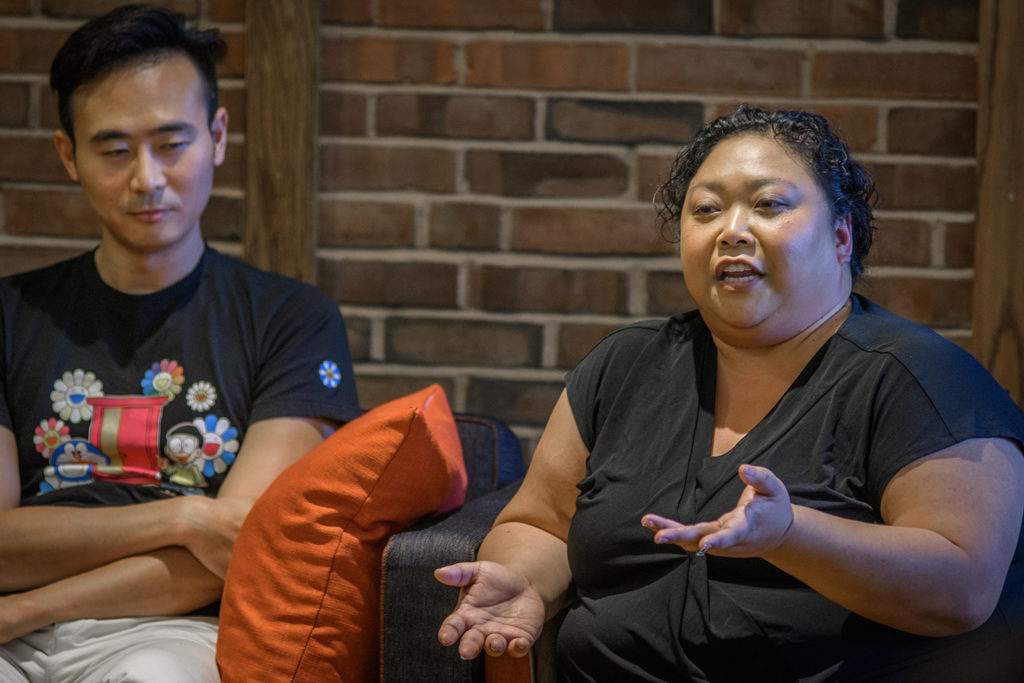 "Professor Lex Jing Lu listens as Maria Gallant speaks at the recent panel discussion on the film ""Crazy Rich Asians"""