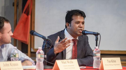 Tun Khin, seated at table, speaks while panelist Matt Wells looks on