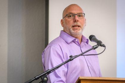 Ken MacLean speaks at lectern