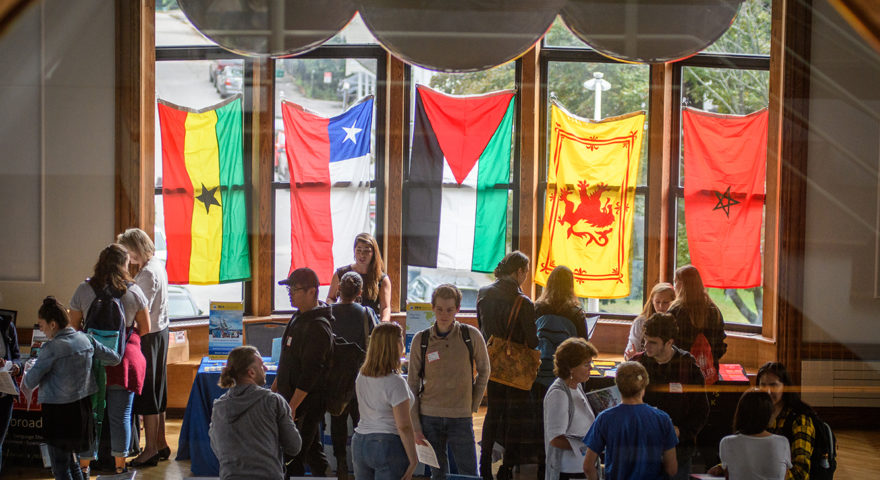 Students at Study Abroad Fair standing in front of windows with flags