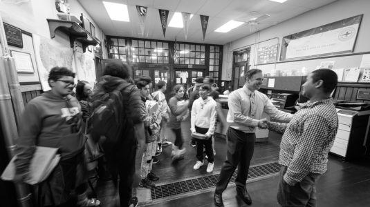 Principal Dan St. Louis '00, M.A.Ed. '01, greets students at the University Park Campus School,
