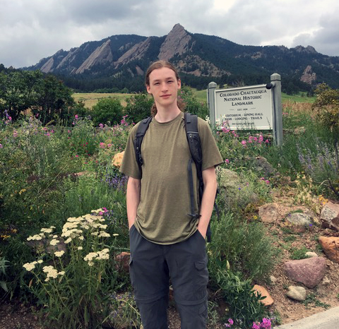 Clement Nagourney stands in field near mountains