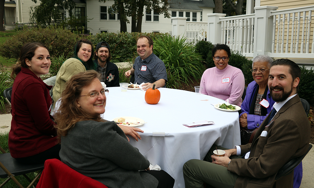 English alumni and faculty seated around table outside