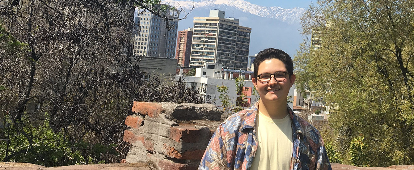 Max DeFaria standing in front of a wall overlooking the city in Chile