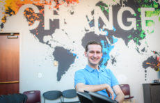 "Curan A. VanDerWielen '21 sits in chair, with words ""Change"" on wall behind him"