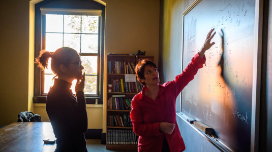 Liana-Shpani works with Physics Professor Barbara Sansone at the blackboard