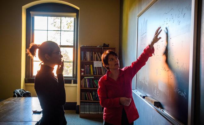 Liana-Shpani works with Physics Professor Barbara Sansone at the blackboard